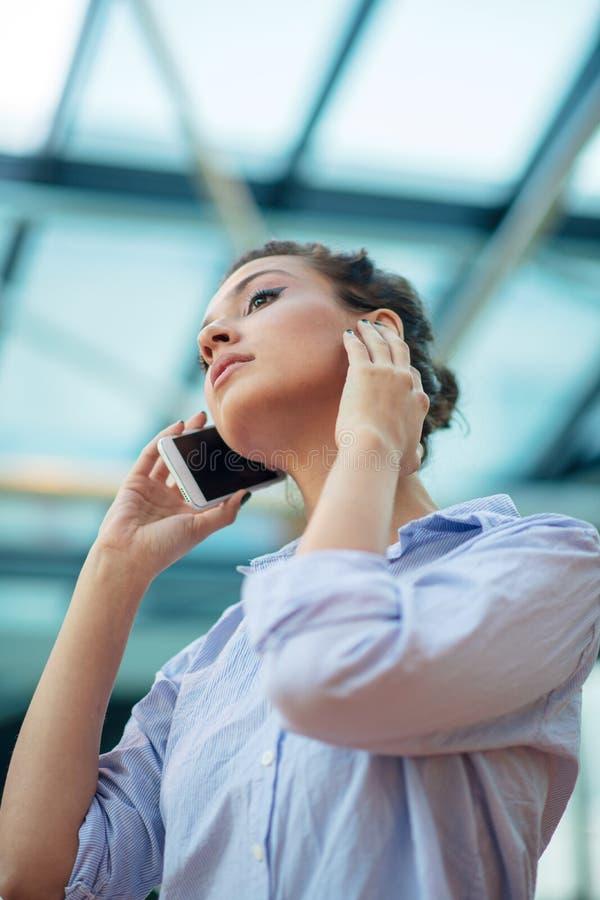 Schitterende vrouw die op mobiele telefoon bij luchthaven spreken royalty-vrije stock foto's