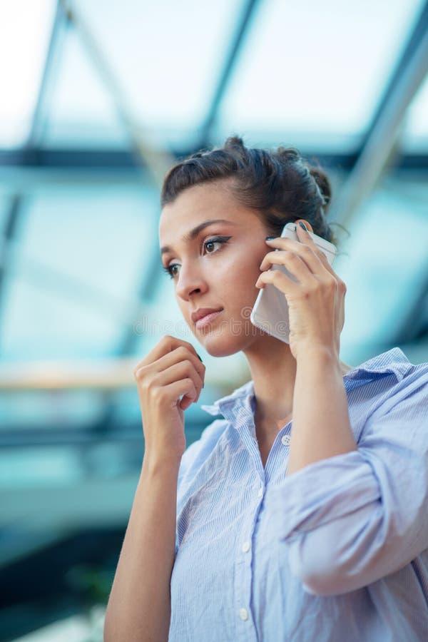 Schitterende vrouw die op mobiele telefoon bij luchthaven spreken stock foto's