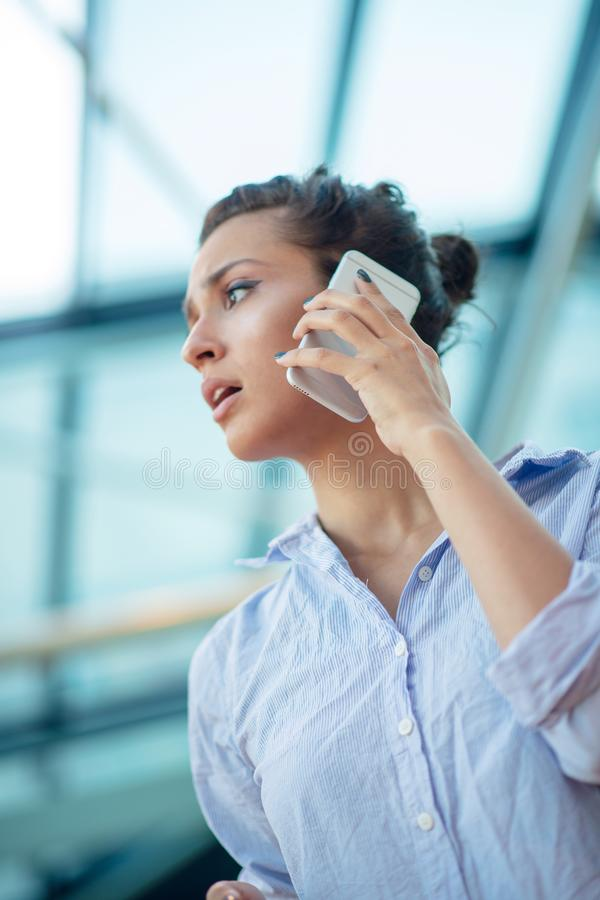 Schitterende vrouw die op mobiele telefoon bij luchthaven spreken stock afbeelding