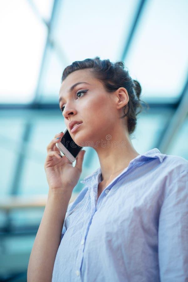 Schitterende vrouw die op mobiele telefoon bij luchthaven spreken royalty-vrije stock fotografie