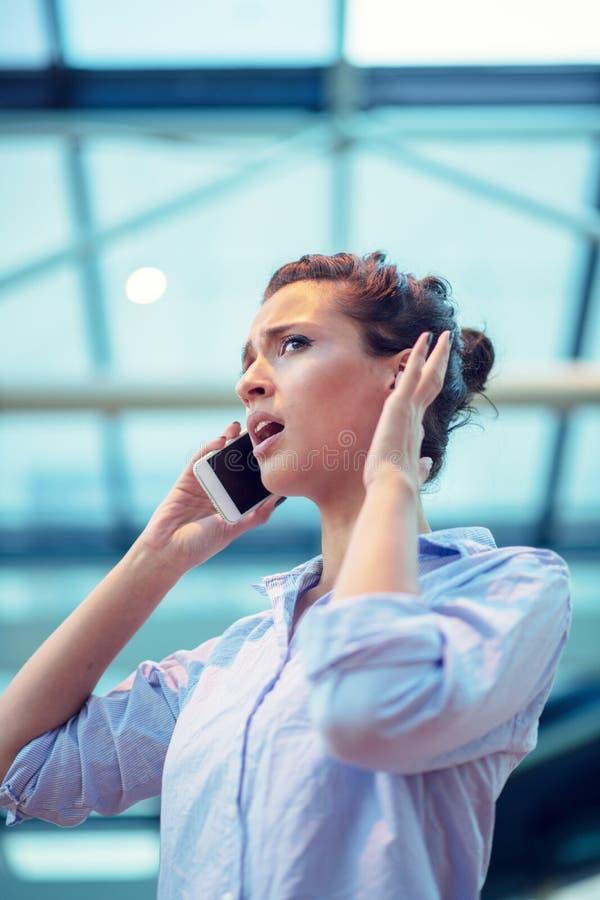 Schitterende vrouw die op mobiele telefoon bij luchthaven spreken royalty-vrije stock foto