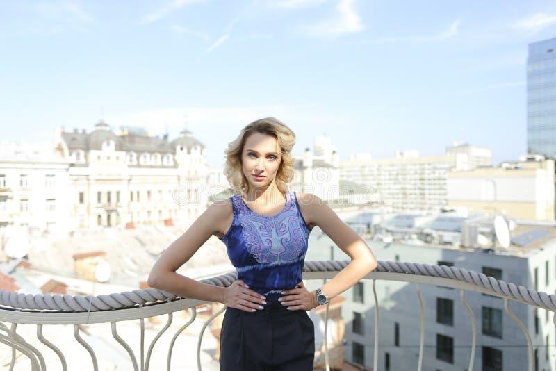 Schitterende vrouw die zich op balkon met buldings op achtergrond bevinden royalty-vrije stock afbeeldingen