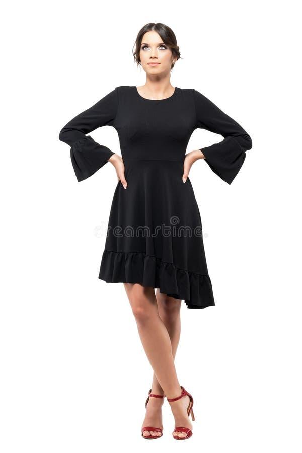 Schitterende vrouw die in zwarte flounce kleding en rode hoge hielen omhoog met wapens op heupen kijken stock foto's