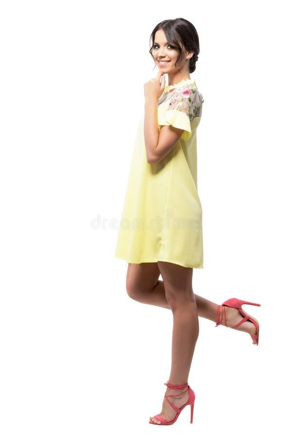 Schitterende vrouw in gele korte de zomerkleding die op de muur leunen die bij camera glimlachen stock afbeeldingen