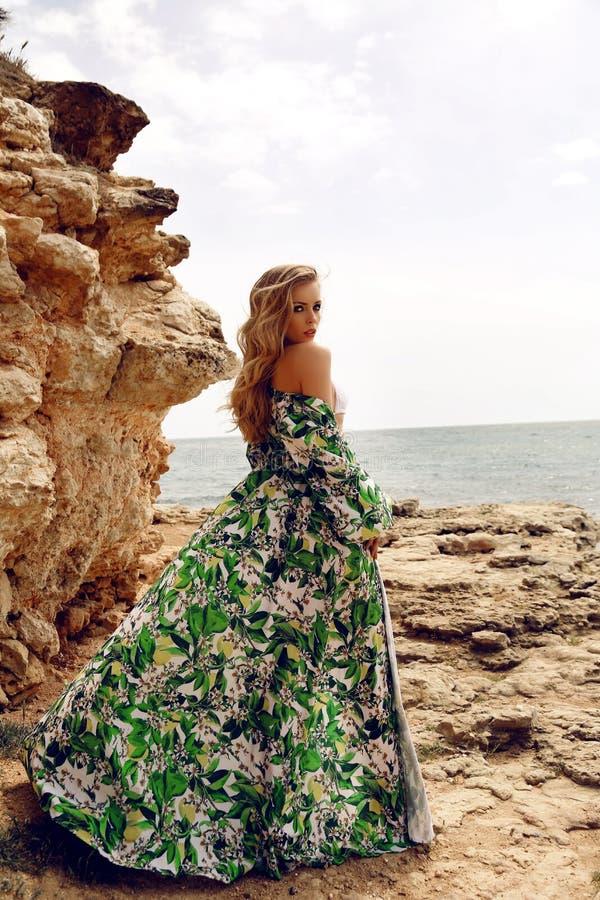 Schitterende vrouw met blond haar in het elegante kleding stellen op strand stock fotografie