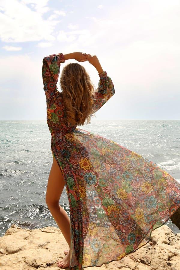 Schitterende vrouw met blond haar in het elegante zwempak stellen op strand royalty-vrije stock afbeeldingen
