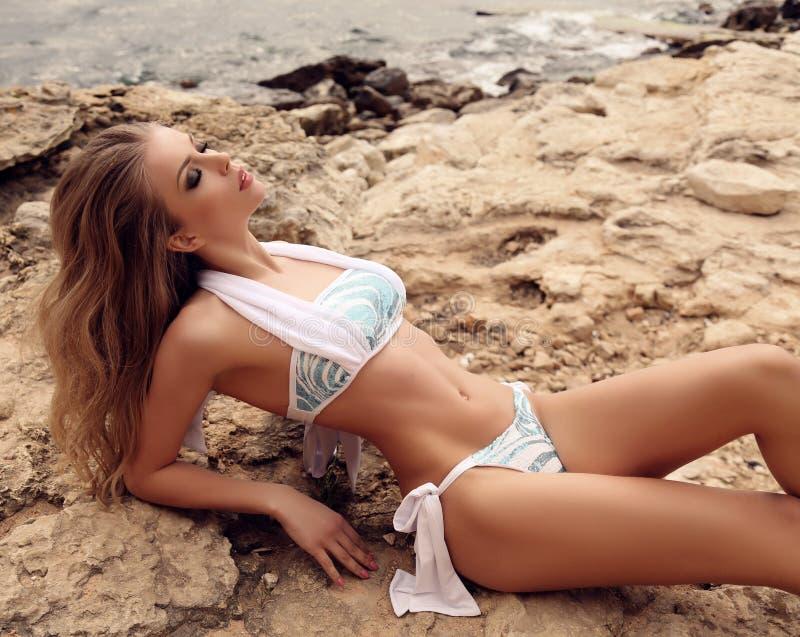 Schitterende vrouw met blond haar in het elegante zwempak stellen op strand royalty-vrije stock afbeelding