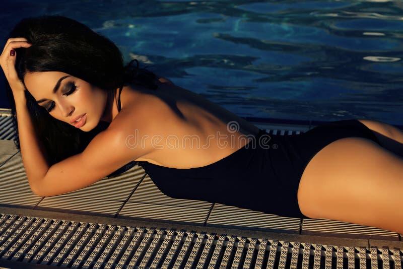 Schitterende vrouw met donker haar in elegant zwempak stock foto