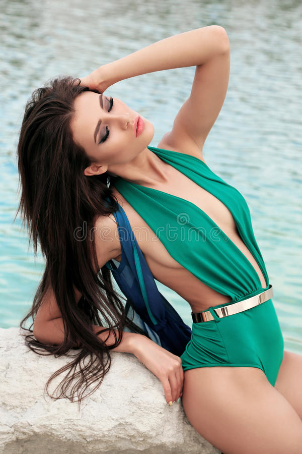 Schitterende vrouw met donker haar in het elegante zwempak stellen op strand royalty-vrije stock fotografie