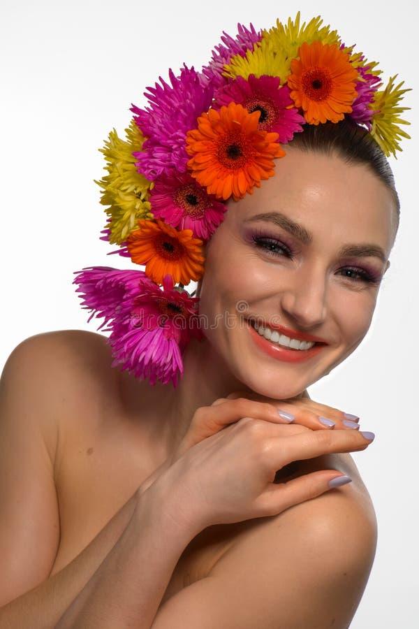 Schitterende vrouw met gerbera één haar hoofdglimlachen royalty-vrije stock afbeeldingen