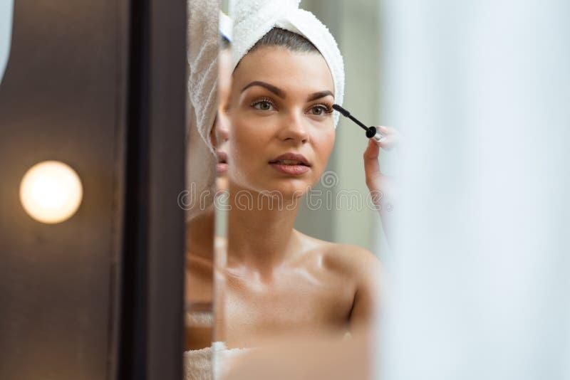 Schitterende vrouwelijke het zetten make-up stock afbeeldingen