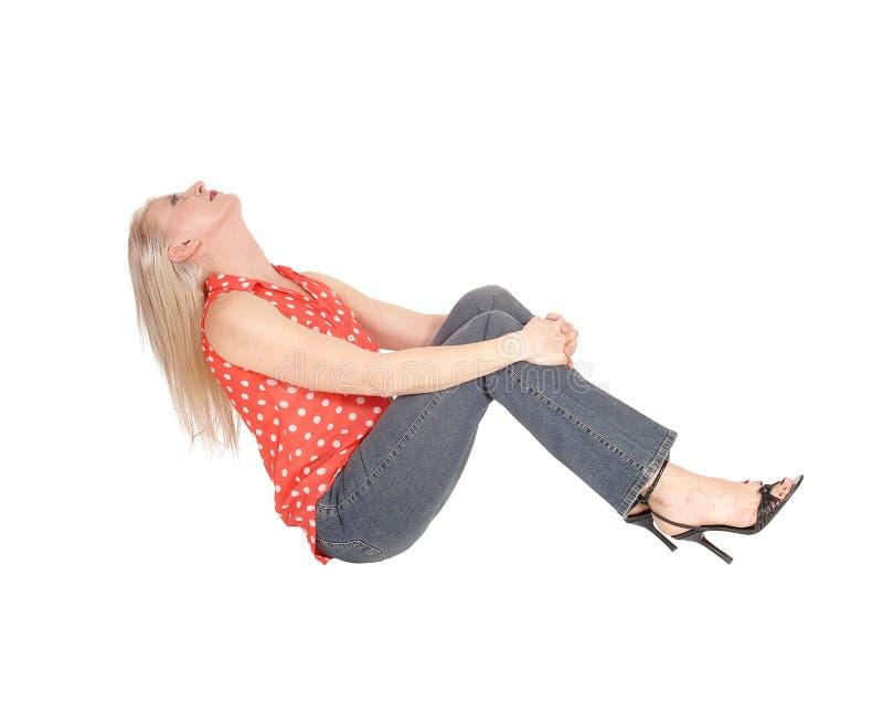 Schitterende vrouwenzitting op de vloer en het lachen royalty-vrije stock foto's