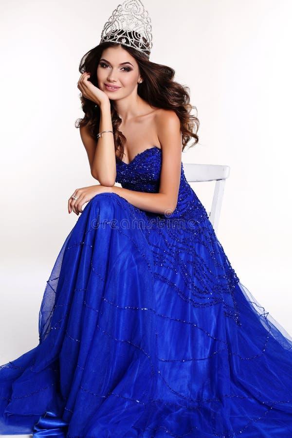 Schitterende winnaar die van schoonheidswedstrijd luxueuze lovertjekleding en kostbare kroon dragen royalty-vrije stock afbeelding