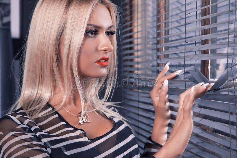 Schitterende witte haarvrouw die met bruine ogen venster bekijken stock afbeelding