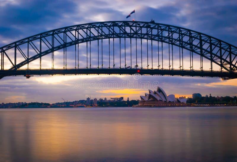 Schitterende zonsondergang die op de machtige brug van staalsydney harbor de oceaan kruisen stock foto's
