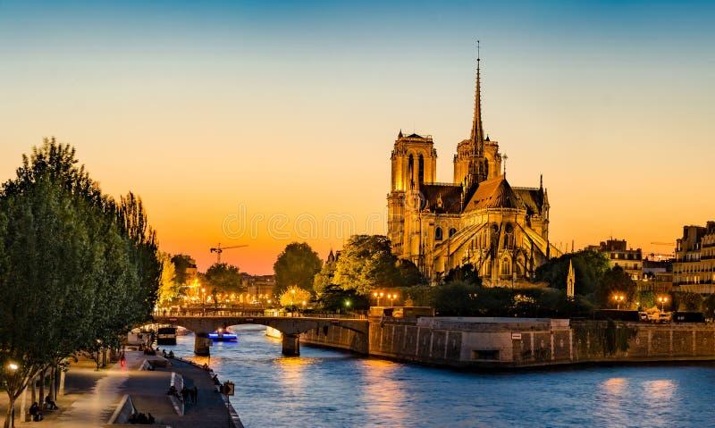 Schitterende zonsondergang over Notre Dame-kathedraal met gezwollen wolken stock afbeelding