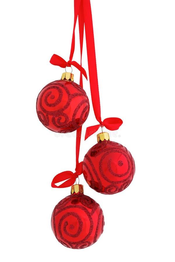 Schittert glanzend rood glas drie Kerstmissnuisterijen die op een rood satijnlint hangen met een geïsoleerde boog, stock afbeeldingen