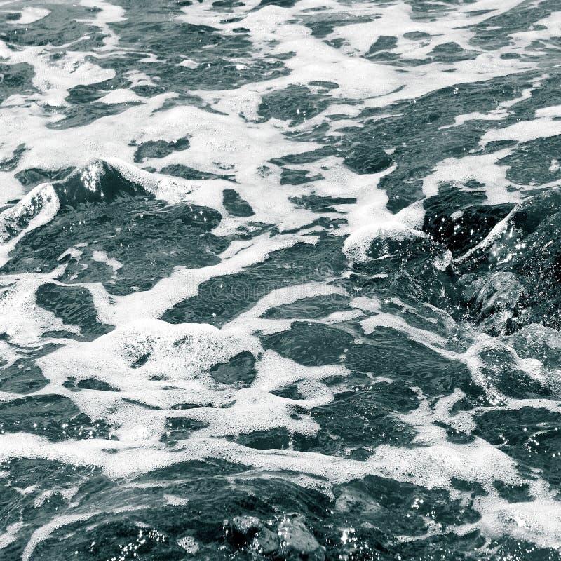 Schiuma bianca sulla superficie dell'acqua di mare cristallina fotografia stock libera da diritti