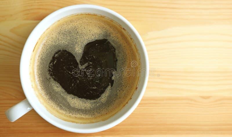 Schiuma calda del caffè nero di forma del cuore, vista superiore con spazio libero sulla tavola di legno per progettazione immagini stock