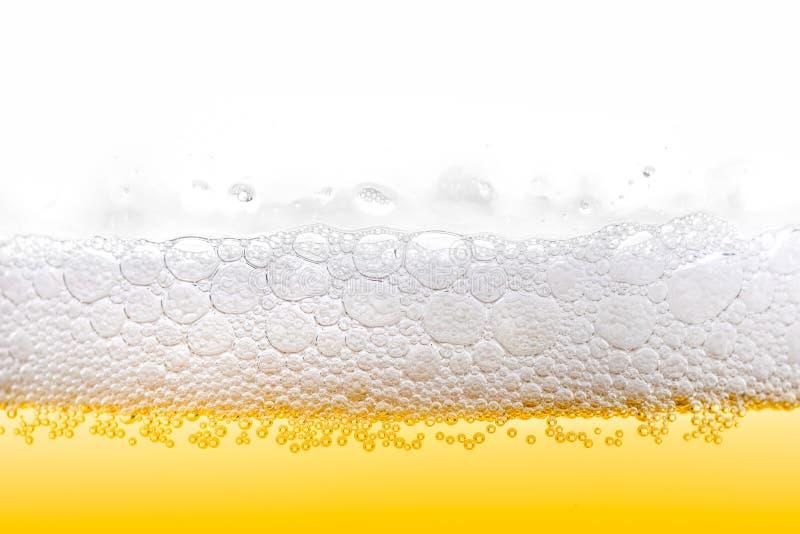 Schiuma ghiacciata della birra dell'oro con il primo piano delle bolle immagine stock