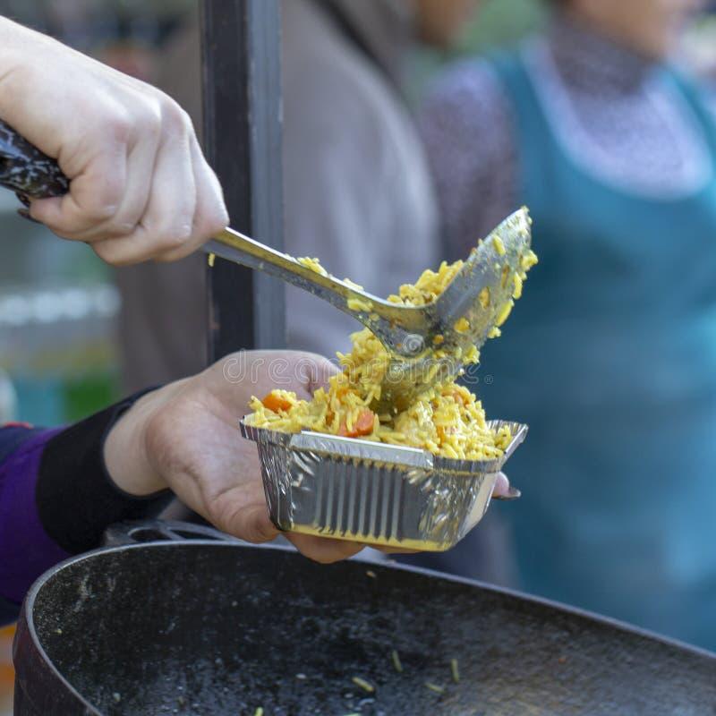 Schiuma nel vassoio alimento di cucchiaio della tenuta della mano nel vassoio della schiuma, streetfood immagine stock libera da diritti
