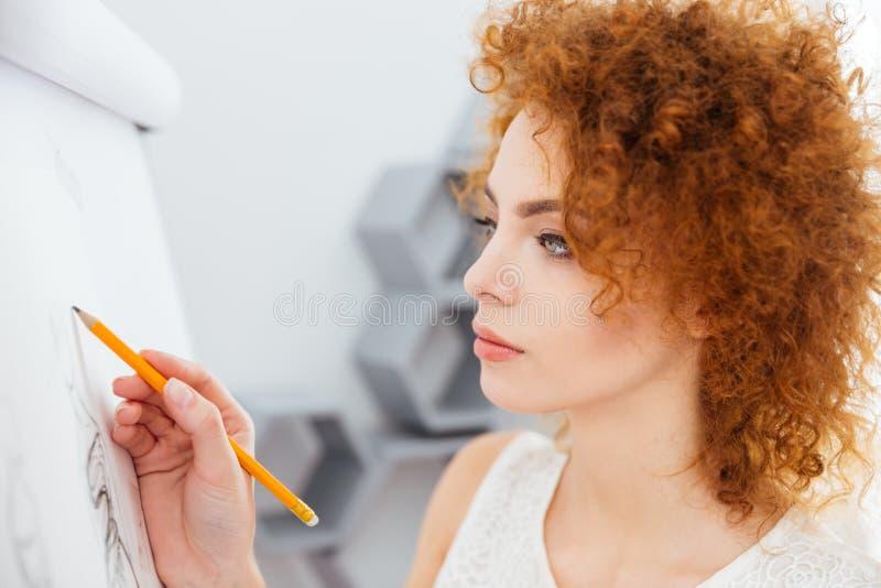 Schizzi attraenti concentrati del disegno dello stilista della giovane donna in ufficio immagine stock
