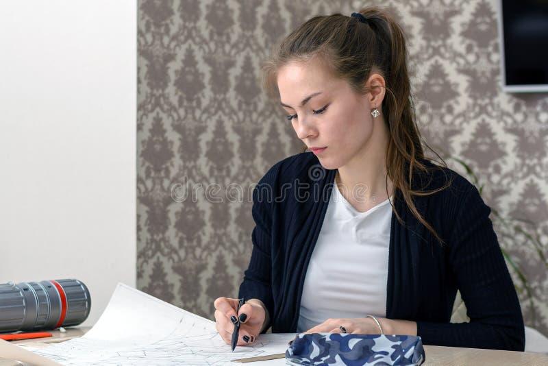 Schizzi concentrati del disegno dell'architetto della studentessa sulla tela bianca che si siede per il desktop interior design e immagine stock