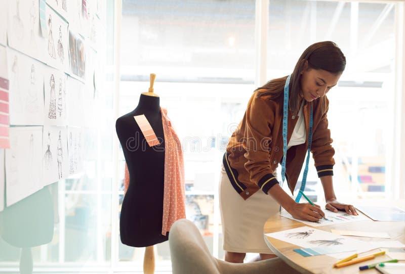 Schizzo femminile del disegno dello stilista sulla tavola in un ufficio moderno immagini stock libere da diritti
