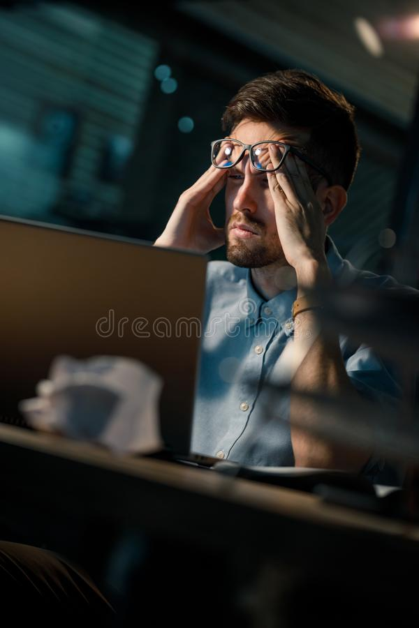 Schläfrige Arbeitskraft, die Laptop verwendet lizenzfreies stockfoto