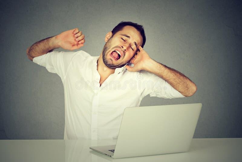 Schläfrige Arbeitskraft mit der gähnenden Laptop-Computer stockfoto