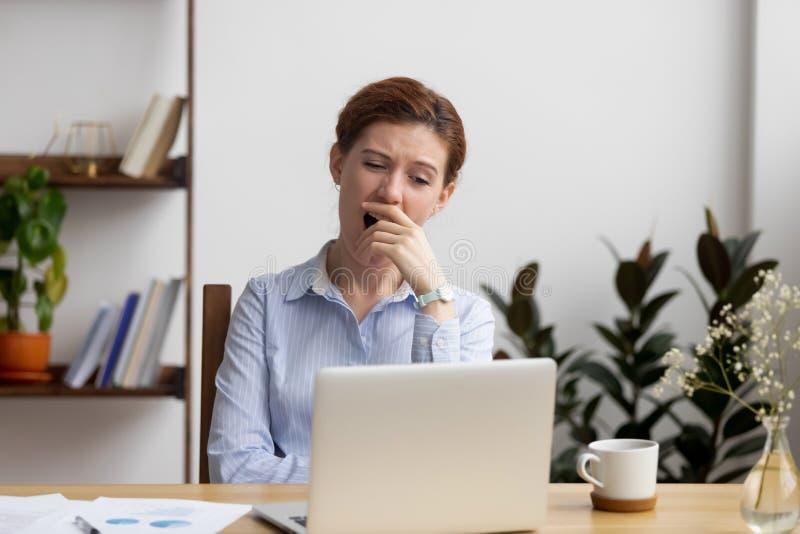 Schläfrige gebohrte Geschäftsfrau, die am Arbeitsplatzgefühl beraubt im Büro gähnt lizenzfreie stockfotos