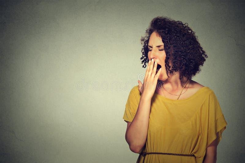 Schläfrige junge Frau mit gähnenden Augen des weit offenen Munds schloss das Schauen gebohrt lizenzfreies stockfoto
