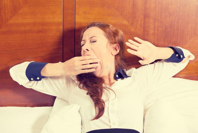 Schläfrige junge gähnende Lügen der Geschäftsfrau im Bett, das versucht aufzuwachen stockfoto