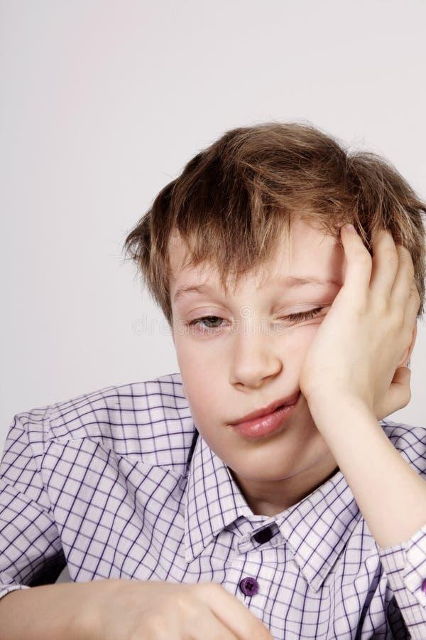 Blonder netter Schüler gebohrt und nach Klasse (Langeweile) ermüdet stockfoto