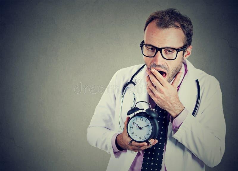 Schläfriger, erschöpfter Doktor, der den Wecker, gähnend hält, ermüdete nach beschäftigtem Tag stockfotografie
