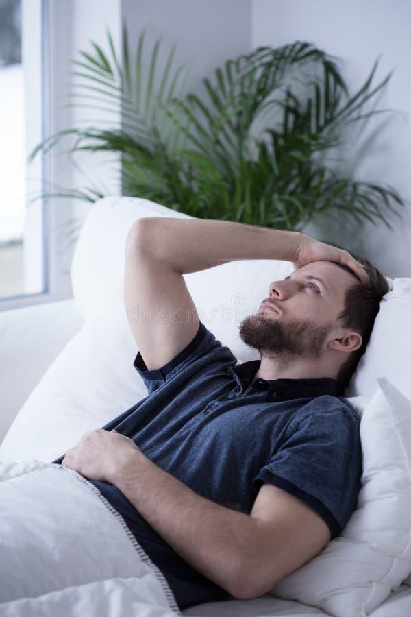 Schläfriger Kerl mit Kopfschmerzen stockbilder