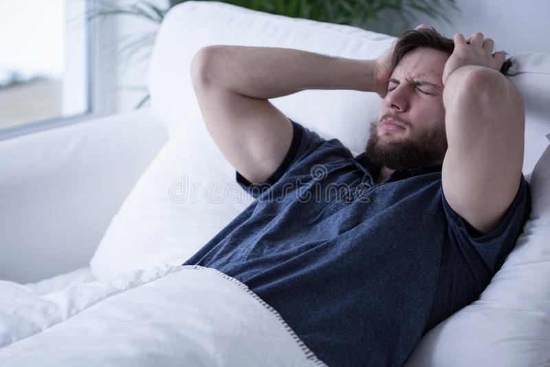 Schläfriger Mann mit Kopfschmerzen lizenzfreies stockbild