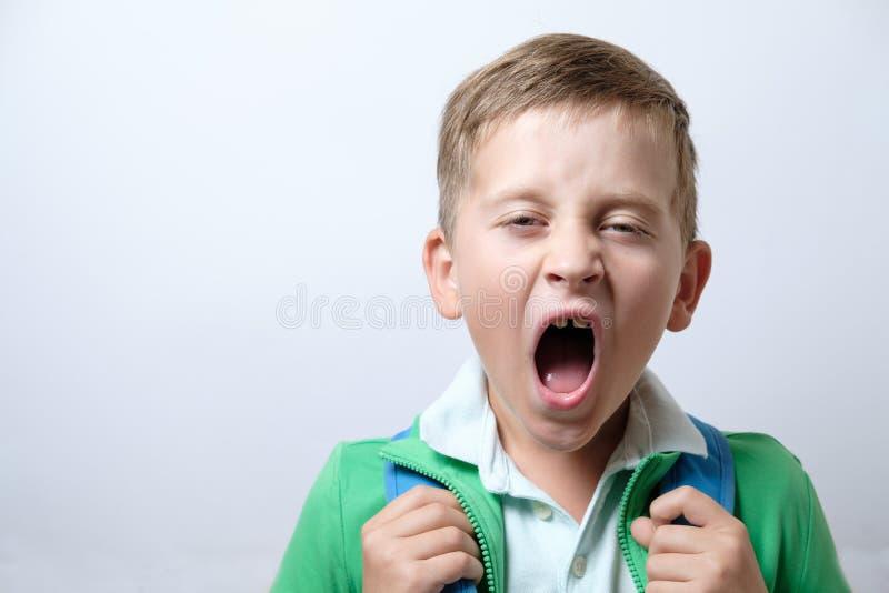 Schläfriger und gähnender Schüler mit blauem Rucksack auf einem weißen backg stockfotos