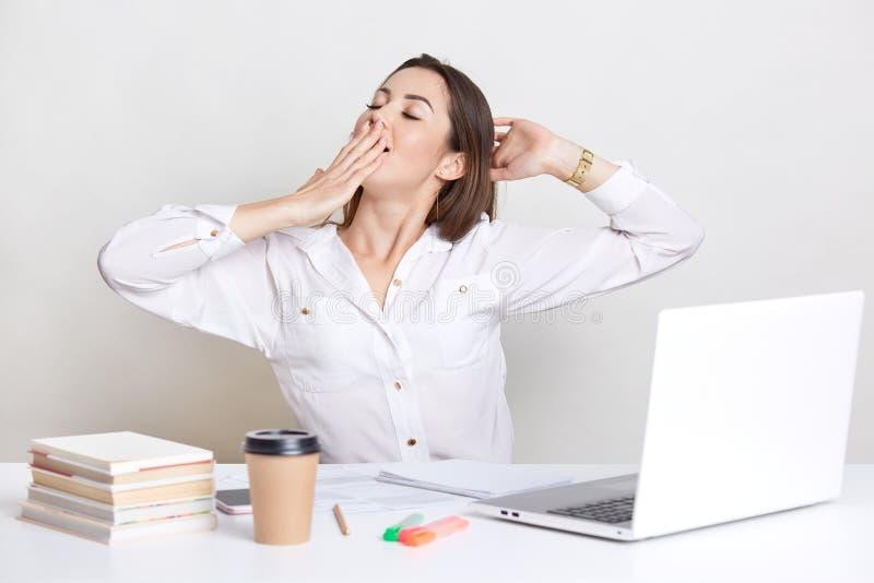 Schläfriges europäisches Frauengegähne und -ausdehnungen, hält Hand auf Mund, trägt weißes Hemd, GebrauchsLaptop-Computer, die Bü stockfoto