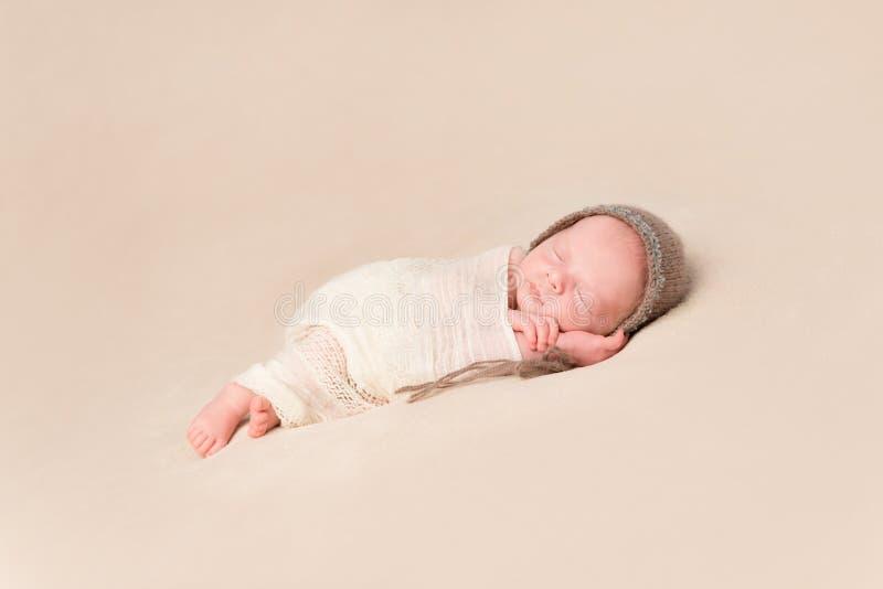Schläfriges gewickeltes neugeborenes Baby in der Strickmütze stockfotografie