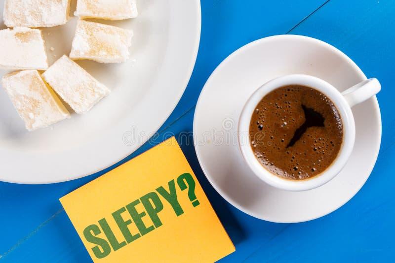 Schläfriges Text-Konzept mit Tasse Kaffee auf dem Tisch stockfoto