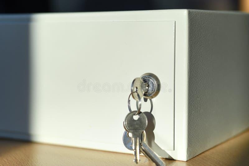 Schlüssel im Verschluss des weißen Safes auf Tabelle im Büro stockfotos