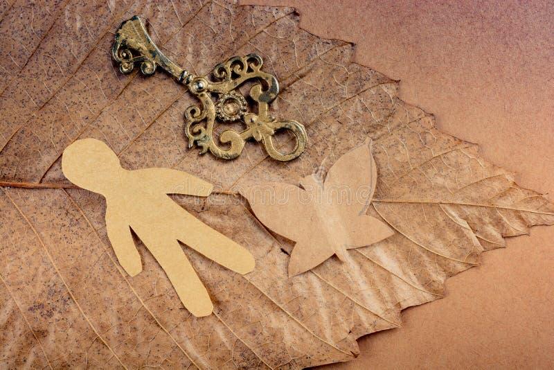 Schlüssel, Mann und ein Schmetterling des Papiers auf einem trockenen Blatt stockbild
