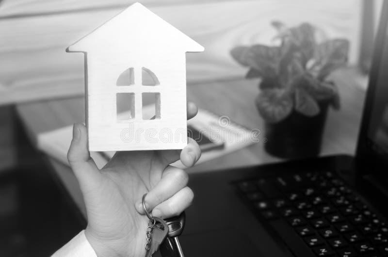 Schlüssel und ein kleines Haus in den Händen Schöne junge kaukasische Frau Konzept von b stockfoto