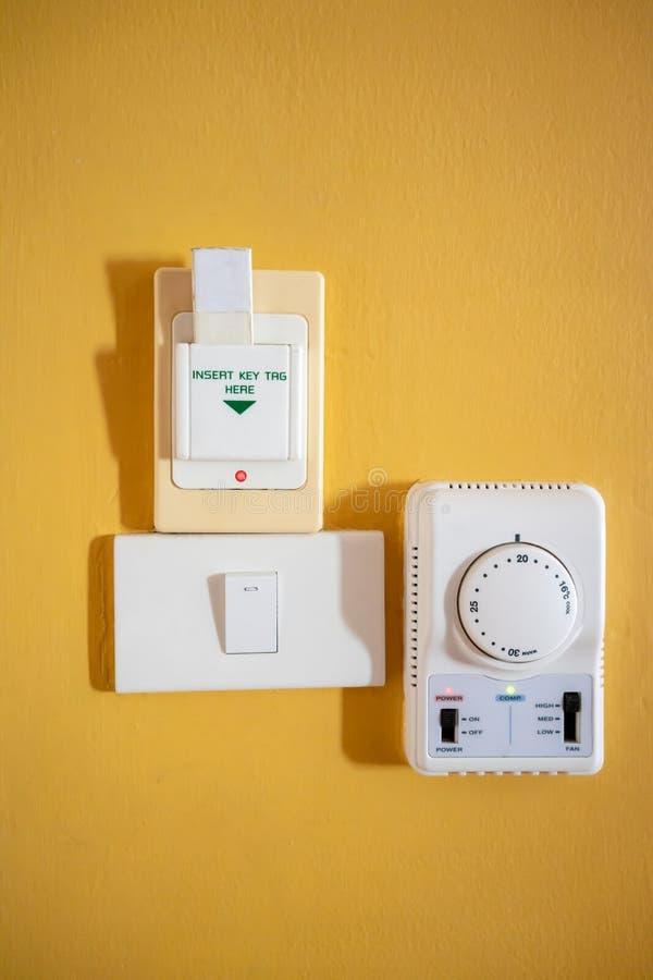 Schlüsselanhänger, Magnetkarte im Schlüsselkasten-Halterschalter gegen gelbes w lizenzfreie stockfotografie