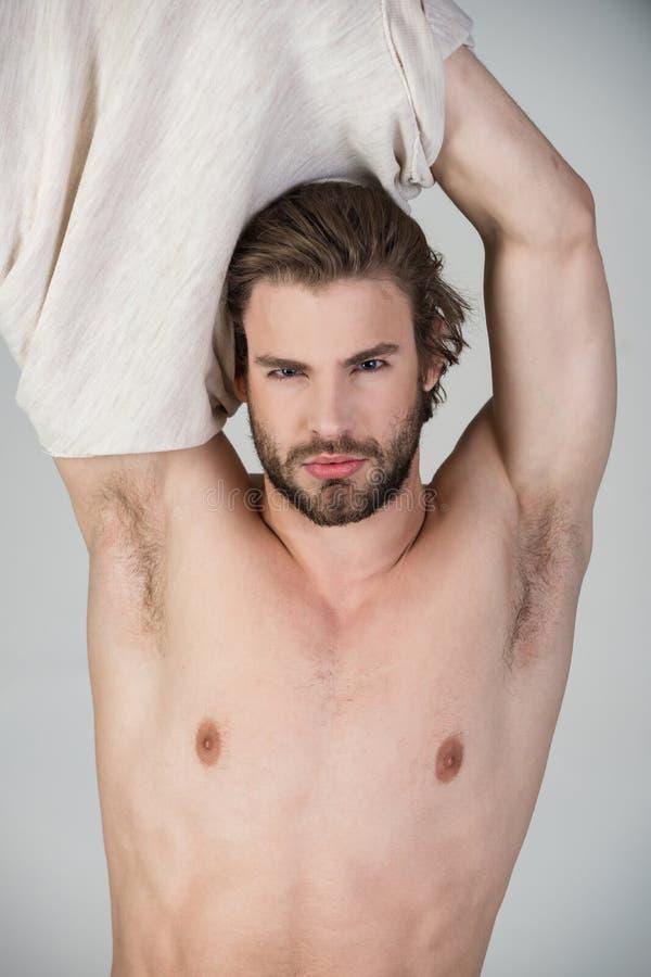 Schl?friger Mann ziehen sich auf grauem Hintergrund aus stockfoto