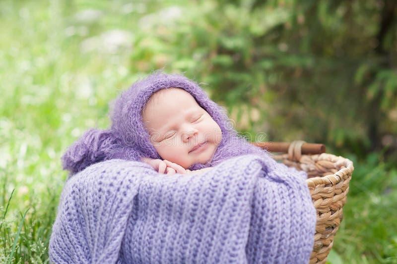 schl?ft eines-Tag-alt l?chelndes neugeborenes Baby 17 auf seinem Magen im Korb auf Natur im Garten im Freien lizenzfreie stockfotos