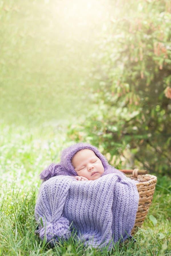 schl?ft eines-Tag-alt l?chelndes neugeborenes Baby 17 auf seinem Magen im Korb auf Natur im Garten im Freien stockbild