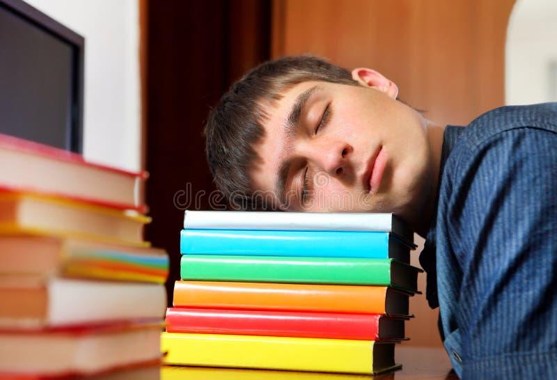 Schlaf des jungen Mannes auf den Büchern lizenzfreie stockbilder