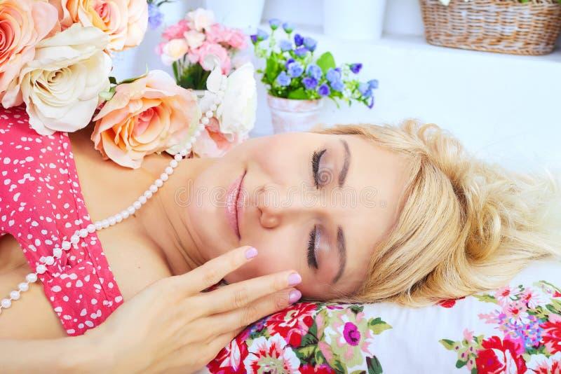 Schlafende blonde Frau, die auf Kissen unter Blumen liegt stockfoto